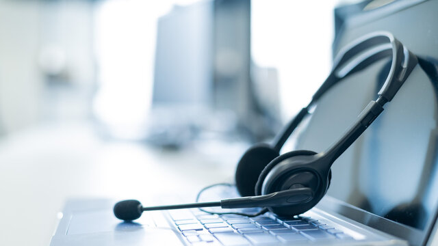 Call center operator desktop. Close-up of a headset on a laptop. Help desk. Workplace of a support service employee. Headphones with a microphone for voip on a computer keyboard.