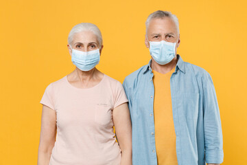 Elderly gray-haired couple woman man in casual clothes sterile face mask isolated on yellow background studio. Epidemic pandemic coronavirus 2019-ncov sars covid-19 flu virus concept. Looking camera.