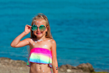 Beautiful little girl in a swimsuit and sunglasses stands by the sea with sunscreen smeared on her...