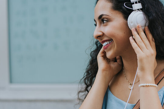 Portrait of smiling teenage girl listening to music outdoors