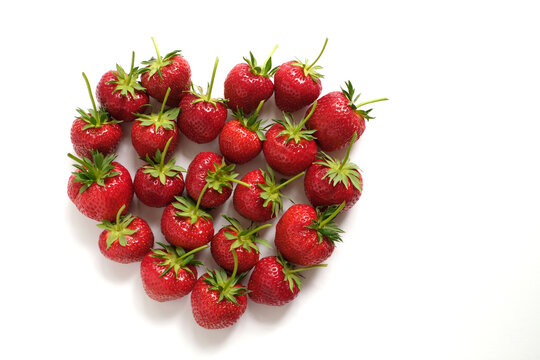 Fresh big strawberries with long stems in heart shaped form