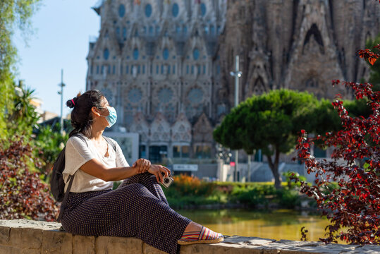 young and pretty tourist woman with face mask posing in front of sagrada familia in barcelona, symbol of tourism to spain during the covid disease and corona virus pandemic