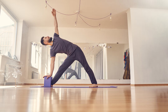 Bearded young man doing exercise with yoga blocks