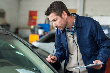 mechanic with clipboard inspecting car
