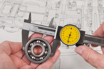 Measurement of steel ball bearing by precise analog caliper above a technical drawing. Metallic measuring tool with round yellow dial in engineer hands. Drafting of combustion engine. Quality control.