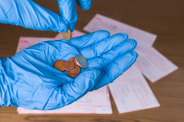 Small metal coins in human hands and money orders on wood desk. Counting euro cash on palm in blue protective glove. Financial problems in COVID-19 pandemic quarantine. Bills payment. Selective focus.