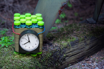 Improvised time bomb planted near metal device on old wood with green moss. Dangerous explosive device with timer or red and blue wire. Violent crime, terrorist act or military attack. Terrorism, war.