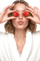 Beautiful tender young girl in a white coat with clean fresh skin posing in front of the camera with strawberries in her hands. Beauty face. Skin care.