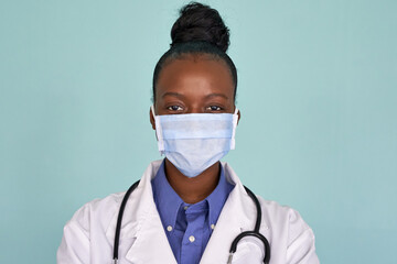 African american female doctor wear white medical coat stethoscope face mask look at camera closeup...