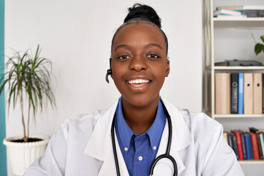 African female doctor wear headset make online telemedicine video call consult patient. Afro american black woman therapist talking to camera in remote videoconference chat. Webcam view, face headshot