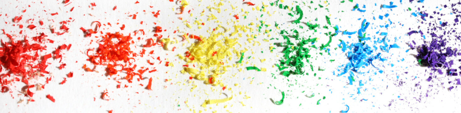 Closeup of pencil shavings against a white background. LGBTQ+ colored flag arrangement. Creative background concept. Inclusivity in the arts
