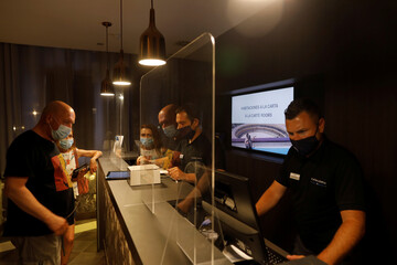 German tourists are attended by receptionists, , wearing protective face masks and with safety measures to prevent the spread of the coronavirus disease (COVID-19), as they do the check-in at the reception desk at Catalonia Ronda hotel, in Ronda