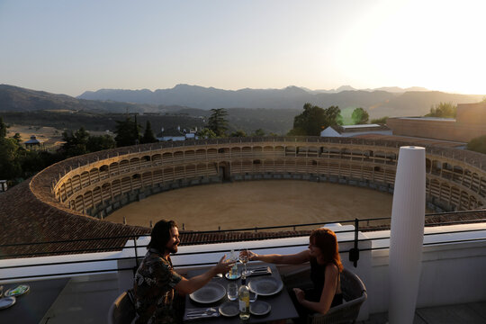 An Australian tourist couple toast with glasses of wine after an easing of restrictions imposed to control the spread of the coronavirus disease (COVID-19), at the terrace restaurant at Catalonia Ronda hotel in Ronda