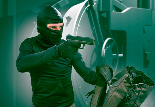 heist and robbery - Hollywood style portrait of man in balaclava mask holding gun in front of security metal vault door in bank or casino heist concept stealing money