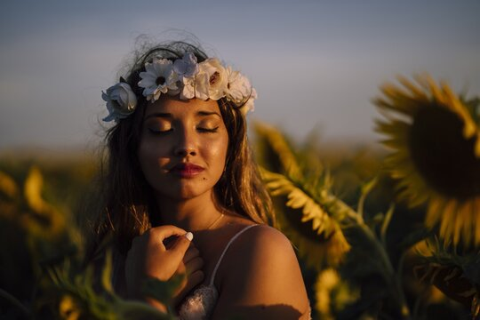 Young brunette female in a flower crown with closed eyes enjoying the sun in a sunflower field
