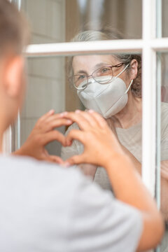 Grandmother wearing protective mask communicates with her grandson through a window during an epidemic of coronavirus. Grandson shows heart sign to grandmother