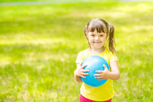 Happy little girl with syndrome down holds ball in a summer park. Empty space for text
