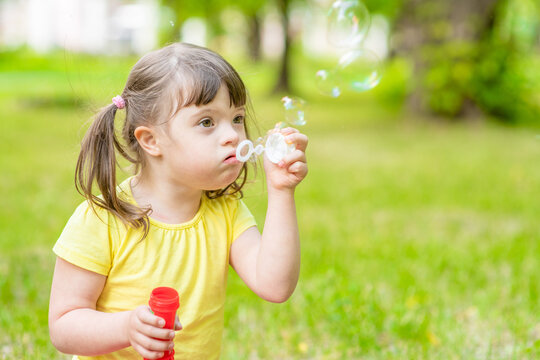 Little girl with syndrome down blows bubbles in a summer park