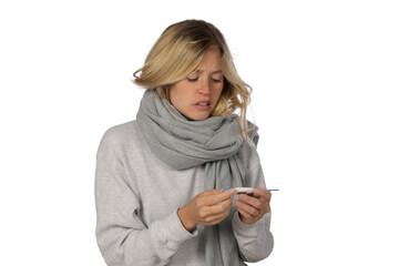Junge Frau sieht krank aus und schaut auf ein Fieberthermometer