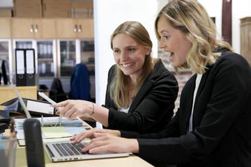 Zwei weibliche Angestellte schauen lachend auf einen Computerbildschirm
