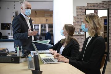 Mitarbeiter eines Büros tragen Masken und unterhalten sich