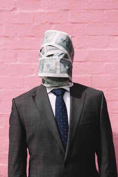Man in a suit with his head wrapped in money paper