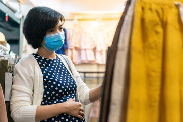 Asian Pregnant woman wear face mask shopping for clothing in a boutique