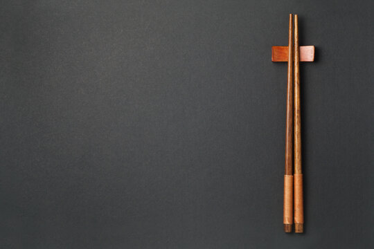 Top view of wooden chopsticks on black paper background