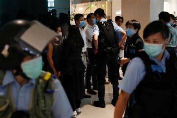 Police officers stop and search demonstrators during a protest after China's parliament passes a national security law for Hong Kong
