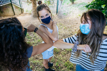 Group of best friends meet in a park and say hi with arms new method for limited contagion from...