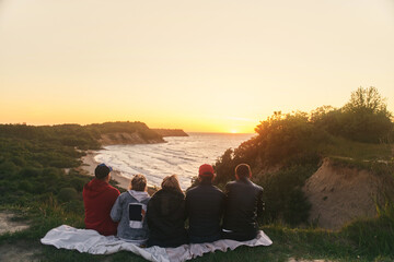 A group of friends watching the sunset at sea. View from the back. High-quality photo