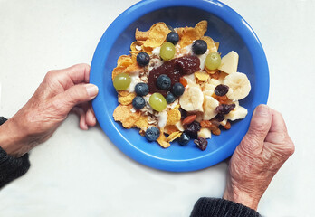 breakfast for senior woman. old hands holding blue plate with cereal and fresh fruits