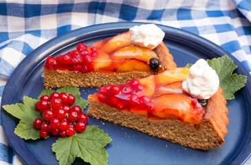 fresh fruit tart with red currants and nectarines on a blue plate