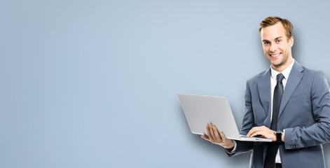 Portrait image of happy smiling businessman working with laptop, standing against grey color background. Success in business concept studio picture. IT professional specialist man.