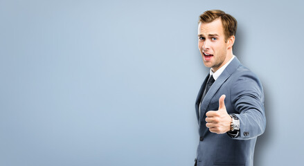 Portrait image - excited businessman showing thumbs up like hand sign gesture, in confident suit, standing over grey background. Amazed man. Copy space for some text or imaginary.