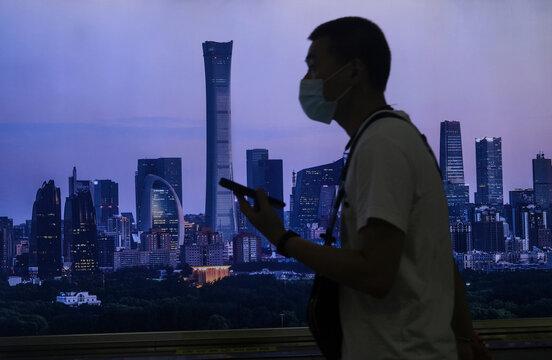Man wearing a face mask walks past a billboard showing Beijing's city skyline at a subway station, following the coronavirus disease (COVID-19) outbreak, in Beijing