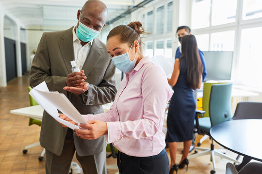 Business people with face mask talk about a document