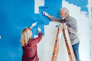 Happy senior couple renovating their home. They are painting a wall together.