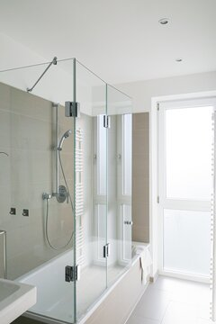 Vertical shot of a modern white bathroom with shower that has glass doors