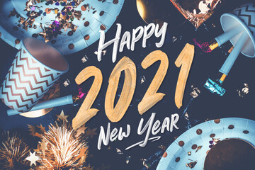 2021 happy new year hand brush storke font on marble table with party cup,party blower,tinsel,confetti.Fun Celebrate holiday party time table top