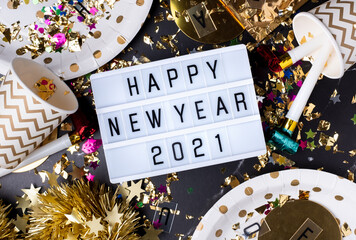 Happy new year 2021 on light box with party cup,party blower,tinsel,confetti.Fun Celebrate holiday party time table top view