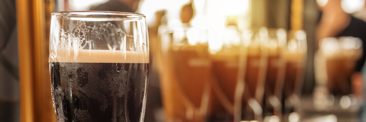 Obraz Close up of a glass of stout beer in a bar - fototapety do salonu