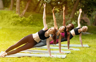 Diverse young women practicing yoga together at park on summer day