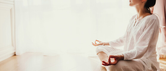 Woman practicing yoga lesson, breathing, meditating Lotus pose with mudra gesture