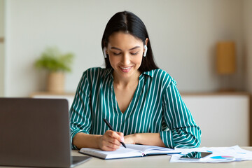 Businesswoman Receiving Call Wearing Earbuds And Taking Notes At Workplace