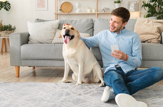Portrait of young man with dog using cell phone
