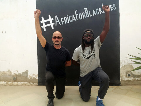 Franco-American photographer Antoine Tempe and an activist and artist Wise Bayano, kneel in front of black wall with #AfricaForBlackLives, in Dakar