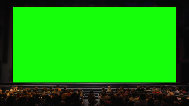 Viewers sitting in front of a big chroma key screen in the auditorium. Audience applauding, light going down
