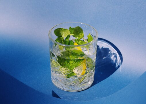 lemonade in crystal glass with fresh mint on blue background