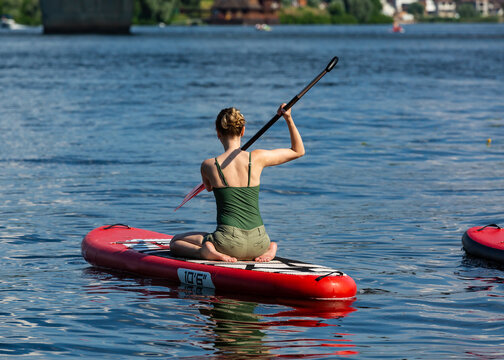 Sup standup paddleboarding.  Woman floats on the river on a board